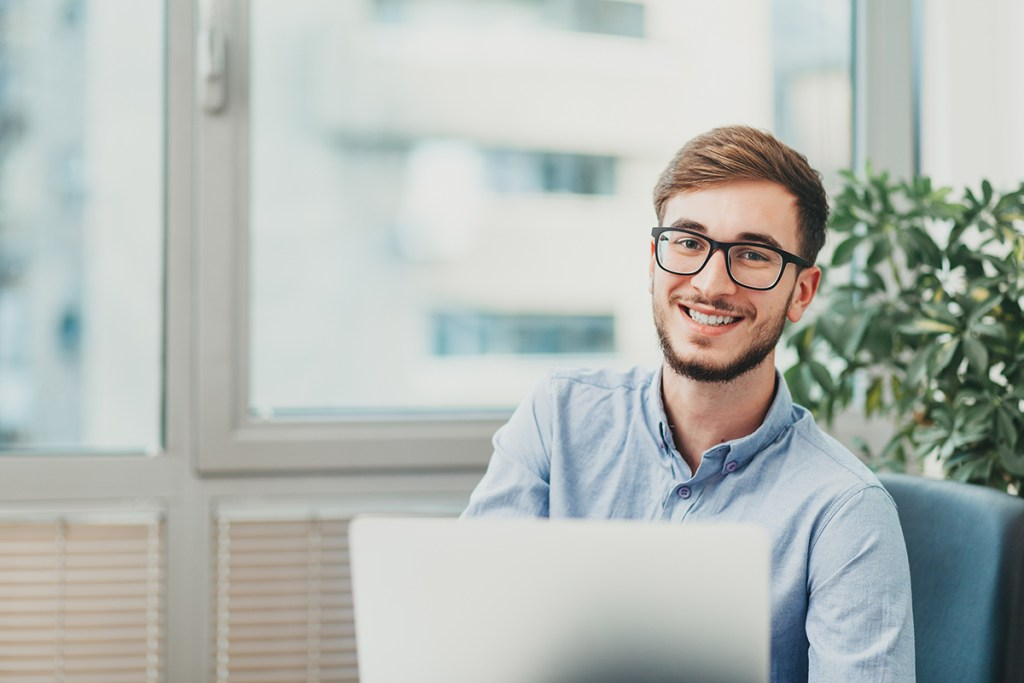 Young male intern with glasses working on laptop and smiling at the camera